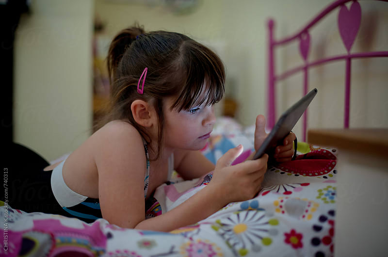 Girl watching her tablet by CHRISTINA K for Stocksy United