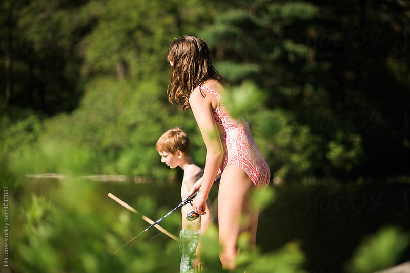 kids fishing by a lake by Léa Jones for Stocksy United