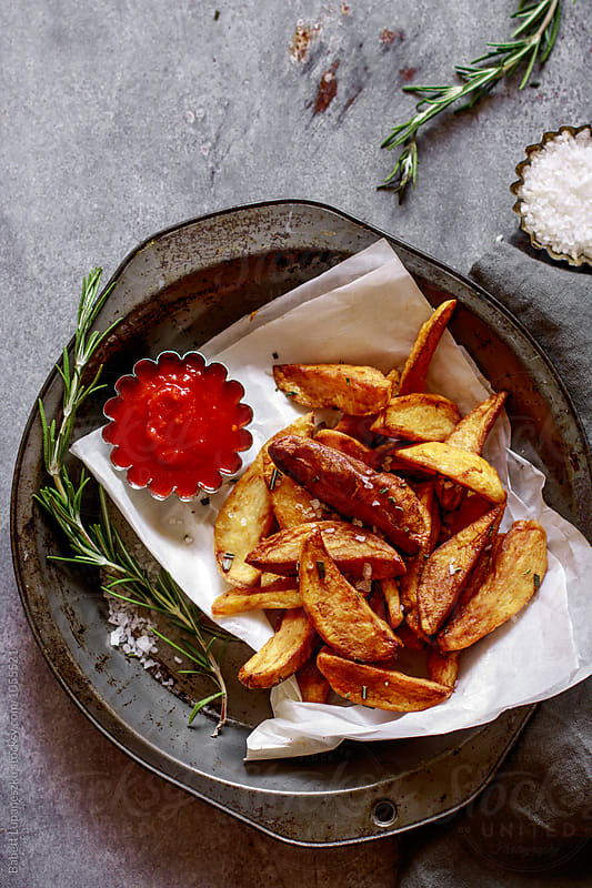 Homemade french fries with sea salt , rosemary by Babett Lupaneszku for Stocksy United