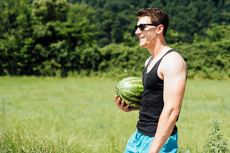 Handsome man holding a fresh watermelon by Boris Jovanovic for Stocksy United
