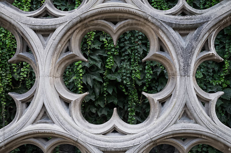 Old stone window contrasted against green foliage by Jon Attaway for Stocksy United