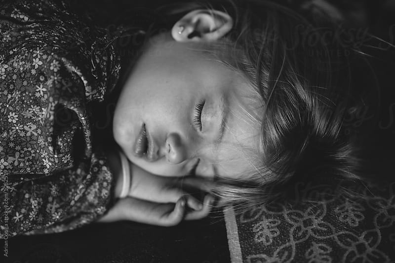 Cute little girl sleeping,  in black and white  by Adrian Cotiga for Stocksy United