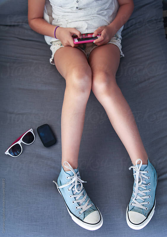 Girl hanging out with her sneakers, glasses and cell phone, texting by Carolyn Lagattuta for Stocksy United