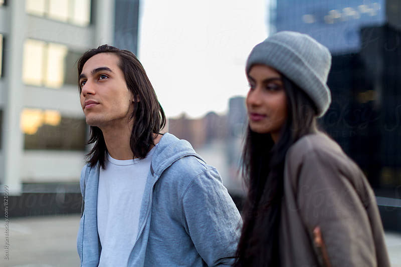Young mixed race couple on rooftop chatting by Ben Ryan for Stocksy United