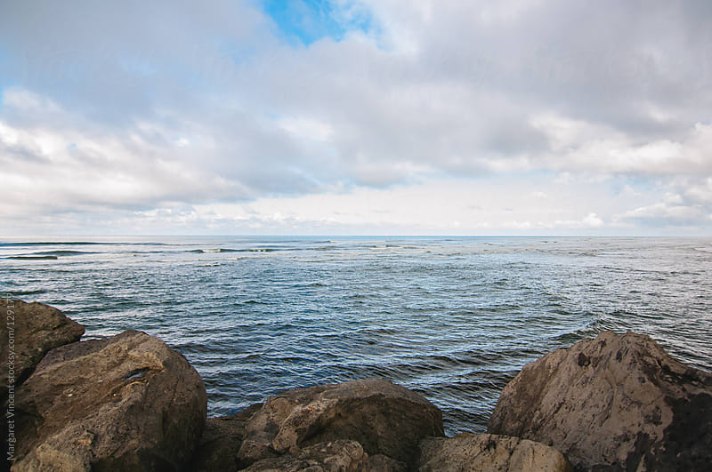 looking out at the ocean from rocks by Margaret Vincent for Stocksy United