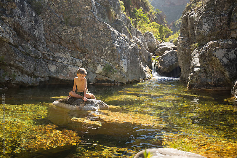 Young boy sits on rock in the middle of mountain stream rockpool near waterfall by Jonathan Caramanus for Stocksy United