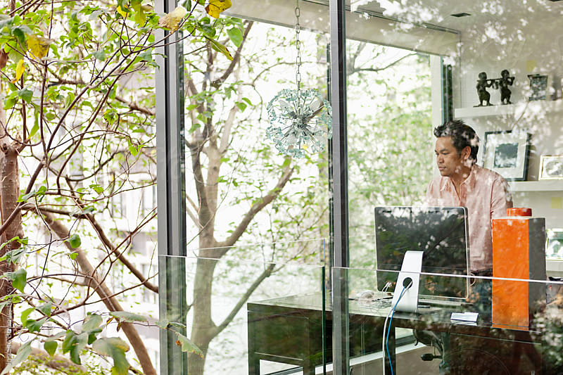 Man in his Fabulous Home Office Surrounded by Trees by Joselito Briones for Stocksy United