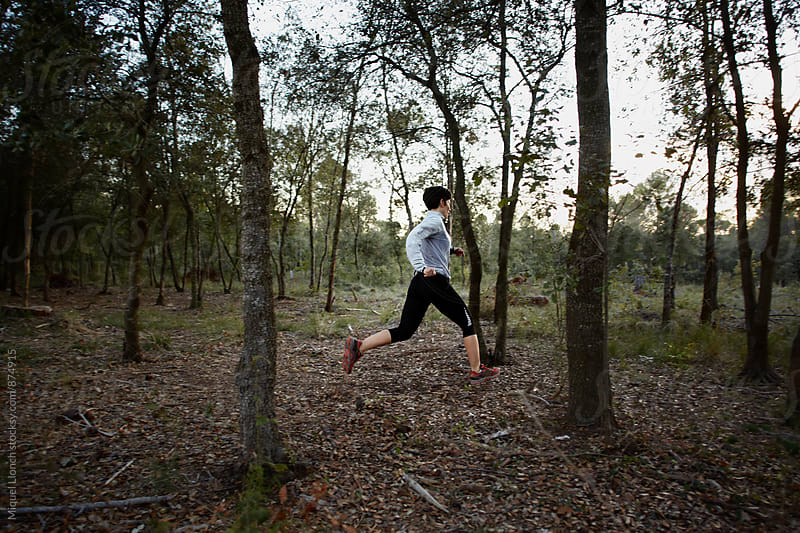 Female running in a forest by Miquel Llonch for Stocksy United