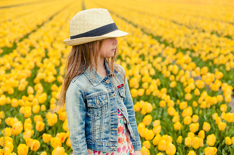 Profile of little girl with straw hat in yellow tulip field by Cindy Prins for Stocksy United