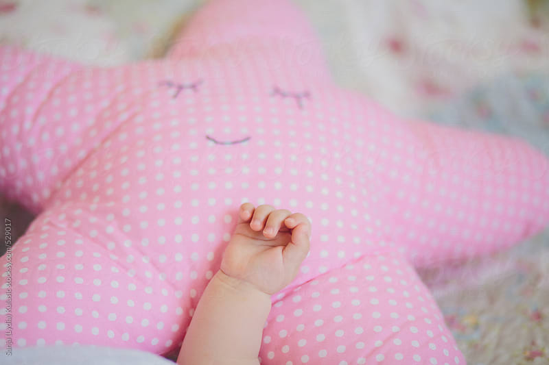 Baby hand on a pink star pillow by Sanja (Lydia) Kulusic for Stocksy United