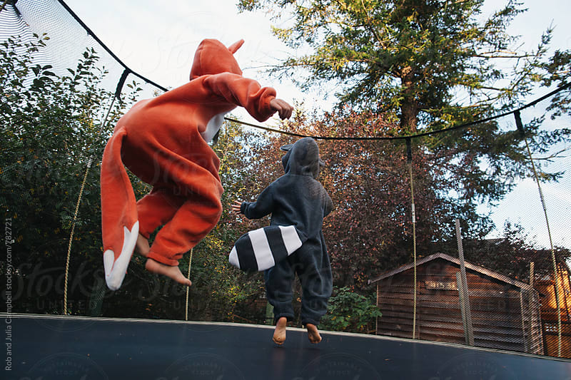 Cute girl in fox and boy in raccoon costume jumping on trampoline by Rob and Julia Campbell for Stocksy United