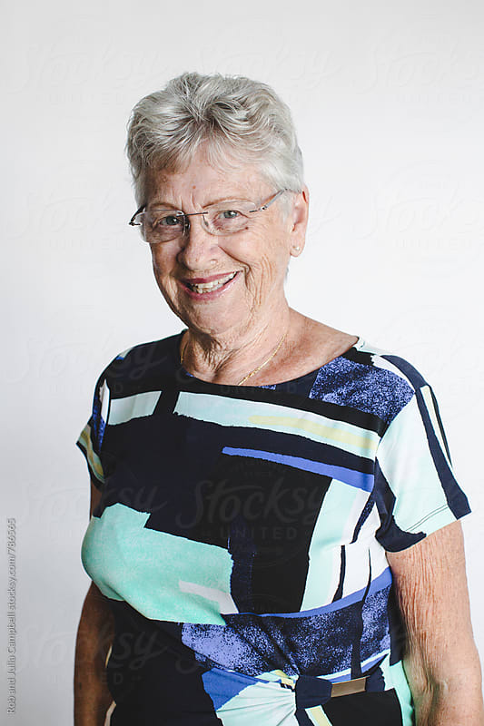 Smiling senior woman on white background by Rob and Julia Campbell for Stocksy United