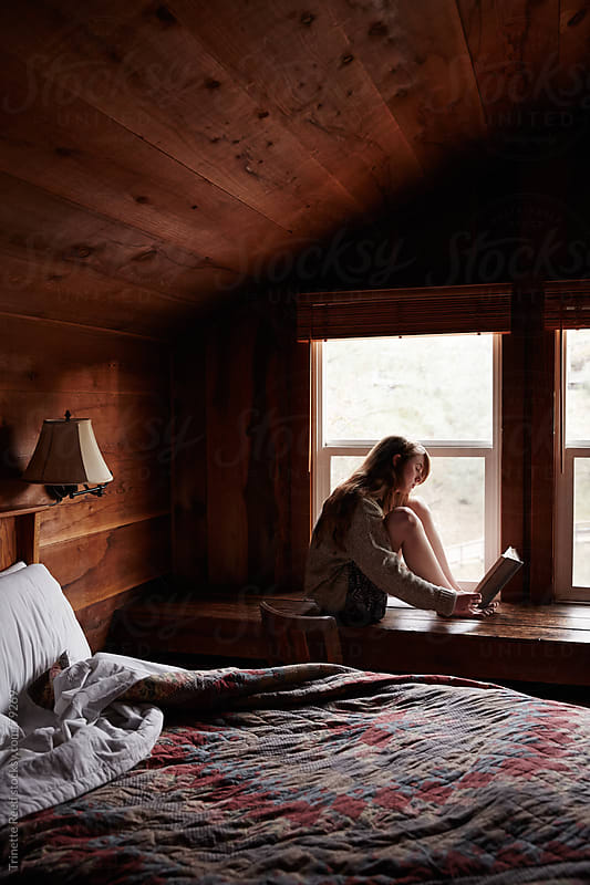 Woman reading a book in cabin bedroom by Trinette Reed for Stocksy United