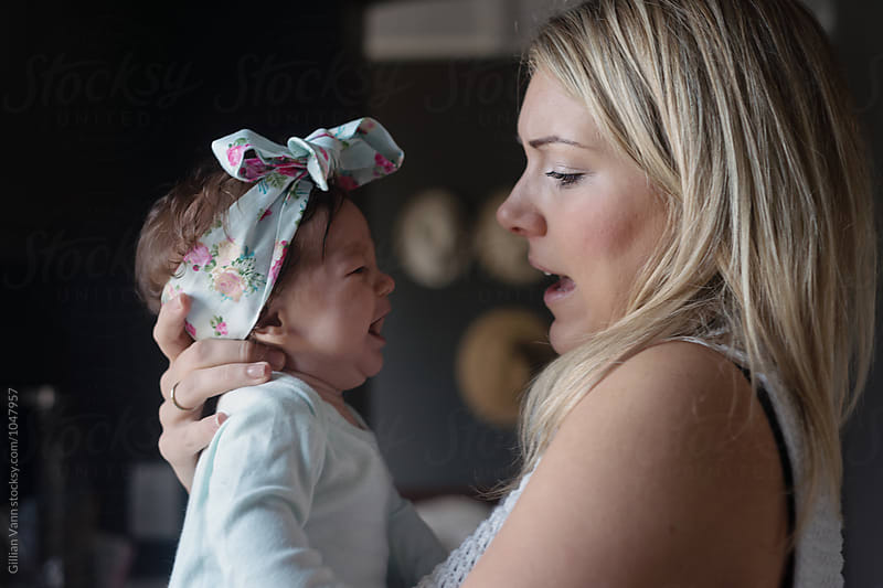 mum comforts her baby as she cries by Gillian Vann for Stocksy United