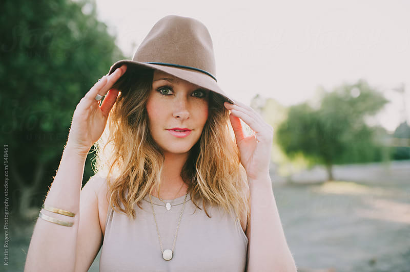 Pretty woman playing with hat at golden hour by Kristin Rogers Photography for Stocksy United