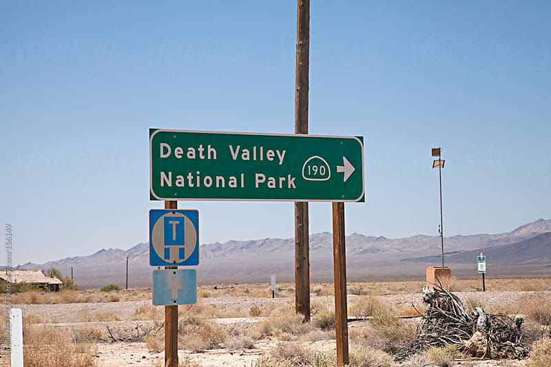 sign post on side of road pointing to Death Valley National Park by Natalie JEFFCOTT for Stocksy United