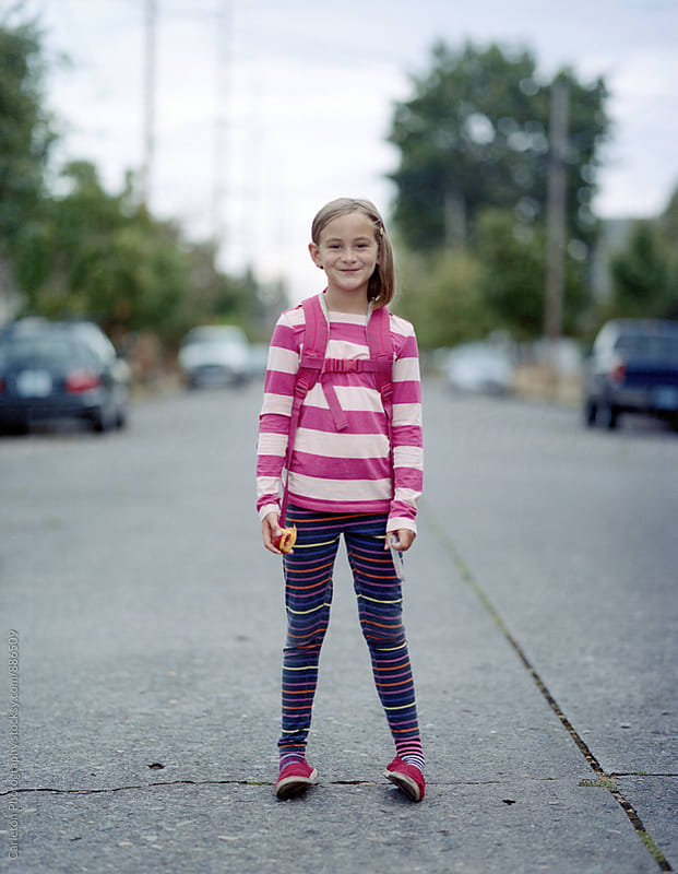 Smilng girl stands in the street with backpack on her back and half eaten peach in hand by Carleton Photography for Stocksy United