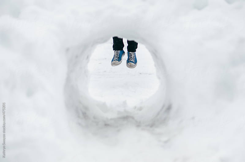A man's jumping feet, as seen through a snow tunnel by Kathryn Swayze for Stocksy United