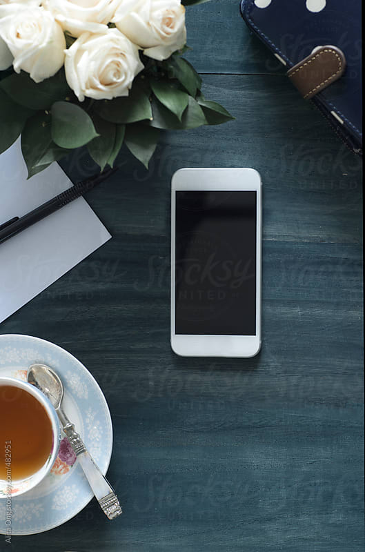 Smartphone and teacup on dark wooden table by Alita Ong for Stocksy United