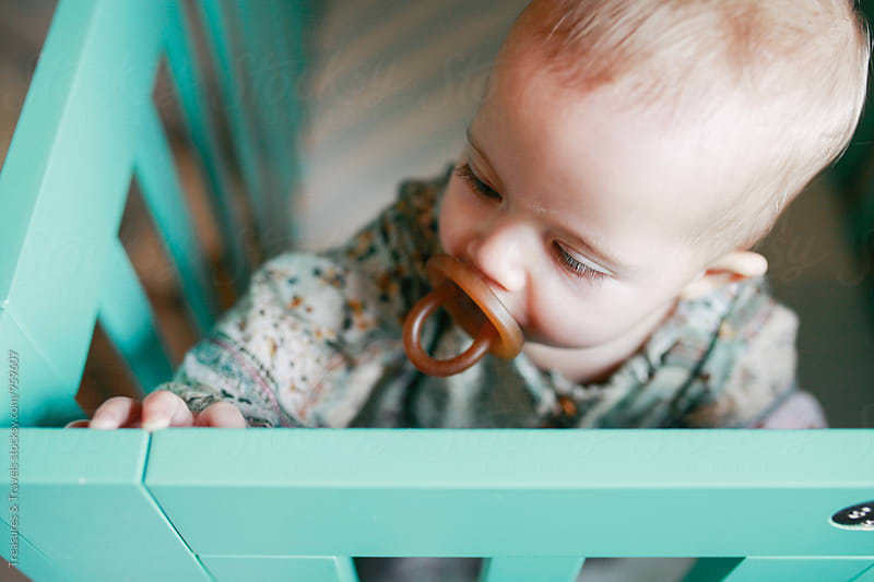 baby in a crib with pacifier in mouth by Treasures & Travels for Stocksy United