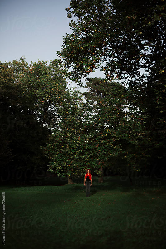 Ginger haired young woman standing alone in the park by Jovana Rikalo for Stocksy United
