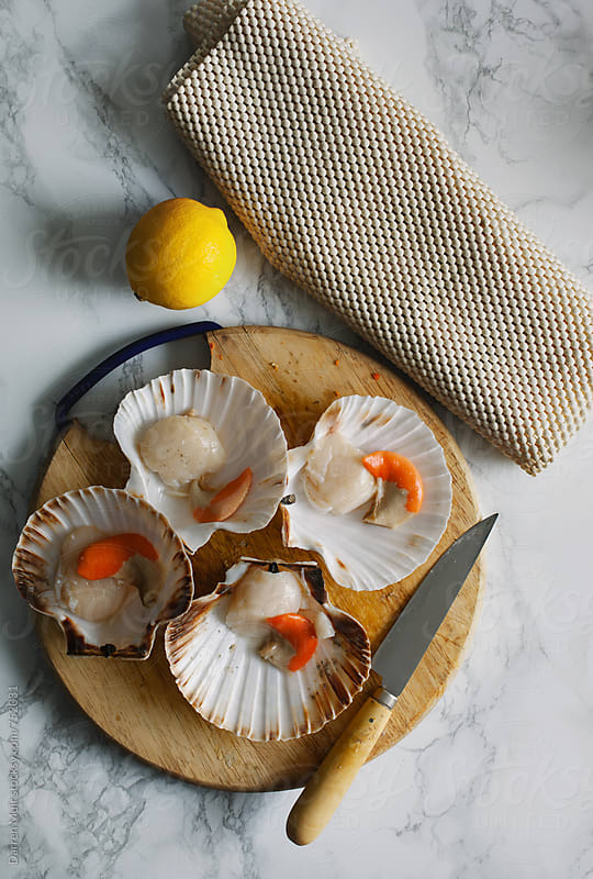Scallops being prepared on a wooden cutting board. by Darren Muir for Stocksy United
