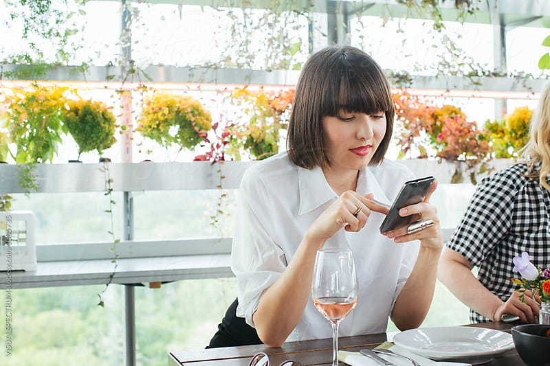 Portrait of Young Brunette Businesswoman Working on Smartphone in Bright Stylish Restaurant by Julien L. Balmer for Stocksy United