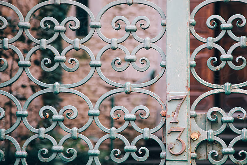 Green wrought iron gate at a house in Florence by Sarah Lalone for Stocksy United