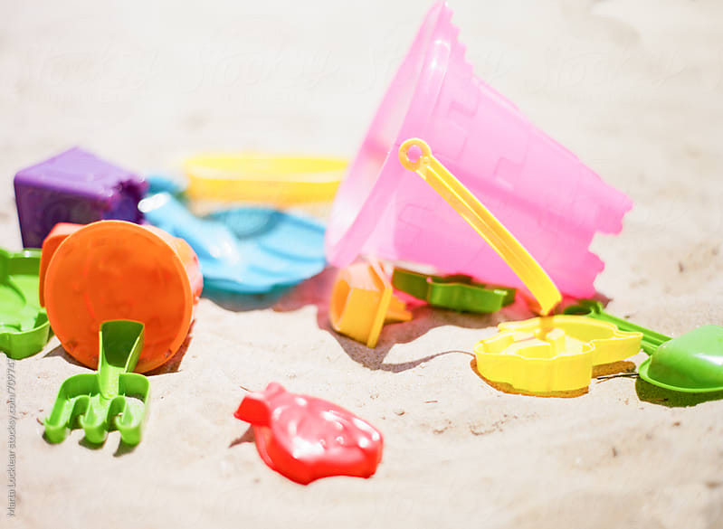 Scattered plastic beach toys by Marta Locklear for Stocksy United