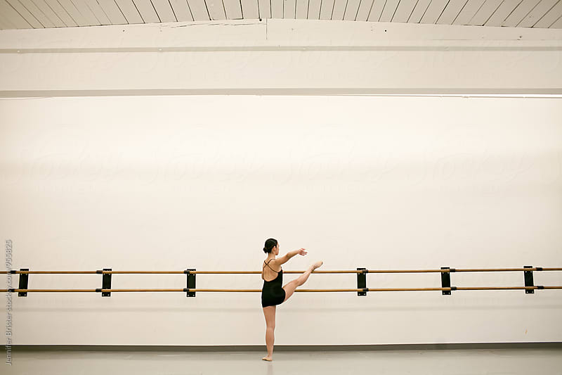 Young dancer stretches in studio by Jennifer Brister for Stocksy United