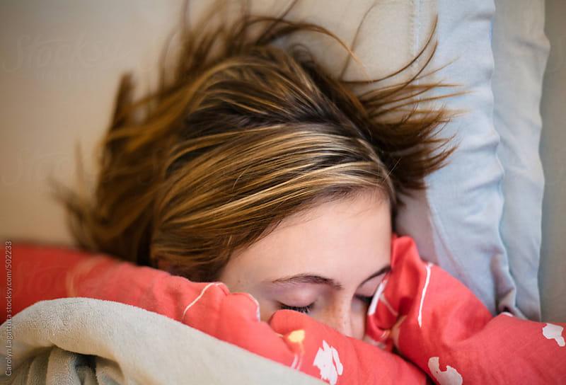 Tired teenage girl sleeping in bed by Carolyn Lagattuta for Stocksy United