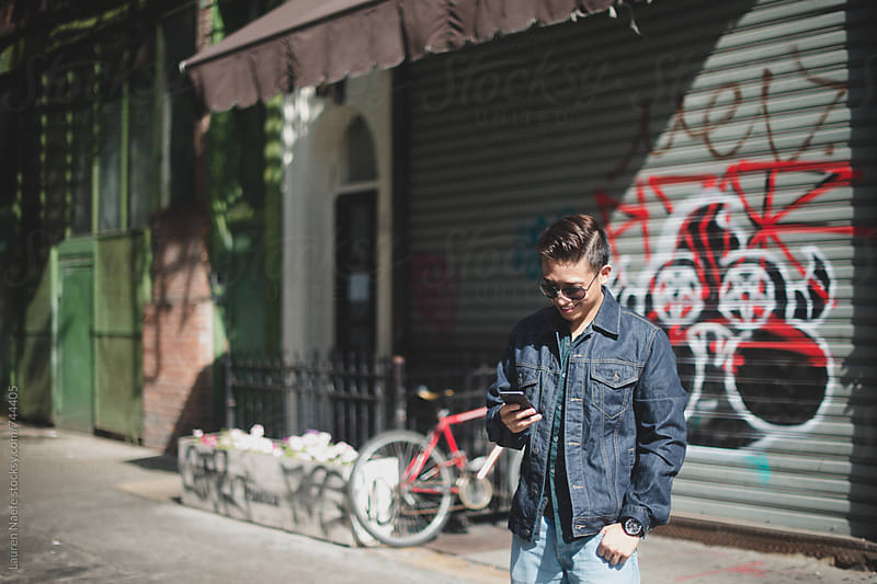 Young man checking cell phone in the city by Lauren Naefe for Stocksy United