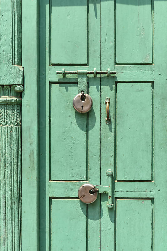 Two padlocks on a green door by Bisual Studio for Stocksy United