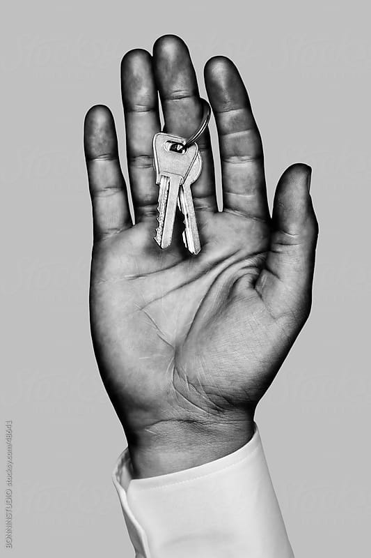 Business hand with two home keys. Black and white by BONNINSTUDIO for Stocksy United
