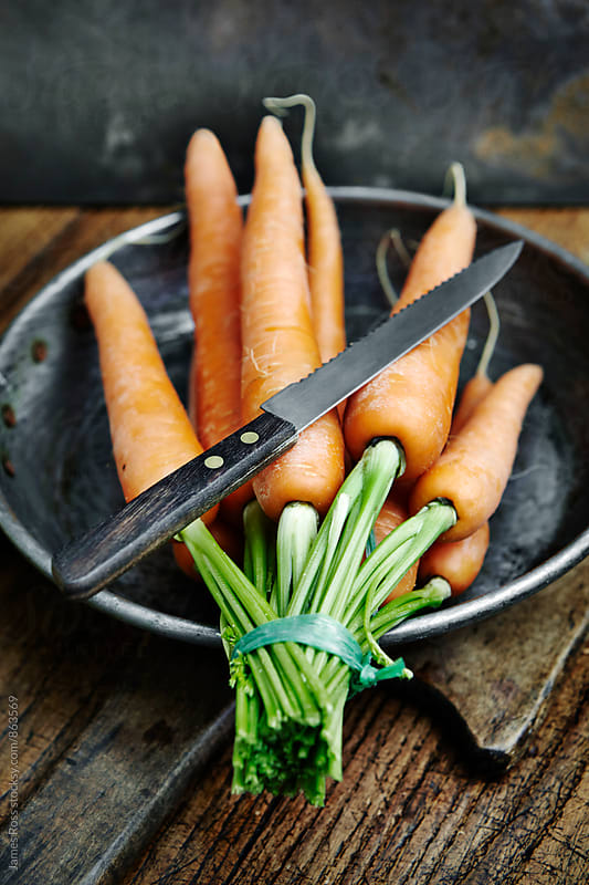 An  bunch of carrots with green tops on a kitchen worktop by James Ross for Stocksy United