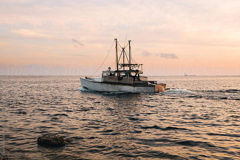 Fishing boat heading to sea by Stephen Morris for Stocksy United