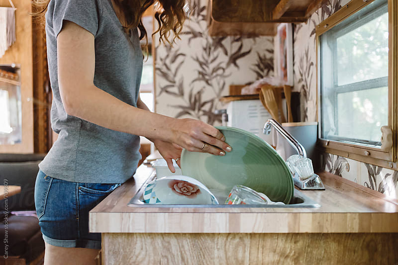 Washing dishes in camper trailer. by Carey Shaw for Stocksy United