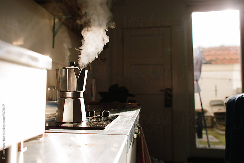Coffee maker blowing seem on a stove in the morning sunlight by Denni Van Huis for Stocksy United