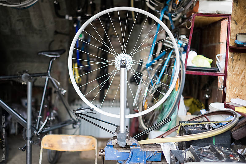 Bicycle Wheel in the Workshop  by Mosuno for Stocksy United