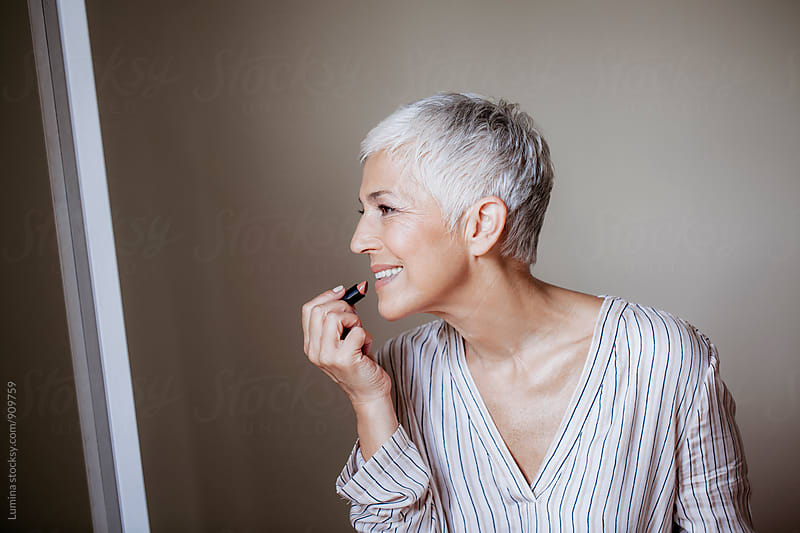 Senior Woman Putting on Make Up in the Morning by Lumina for Stocksy United
