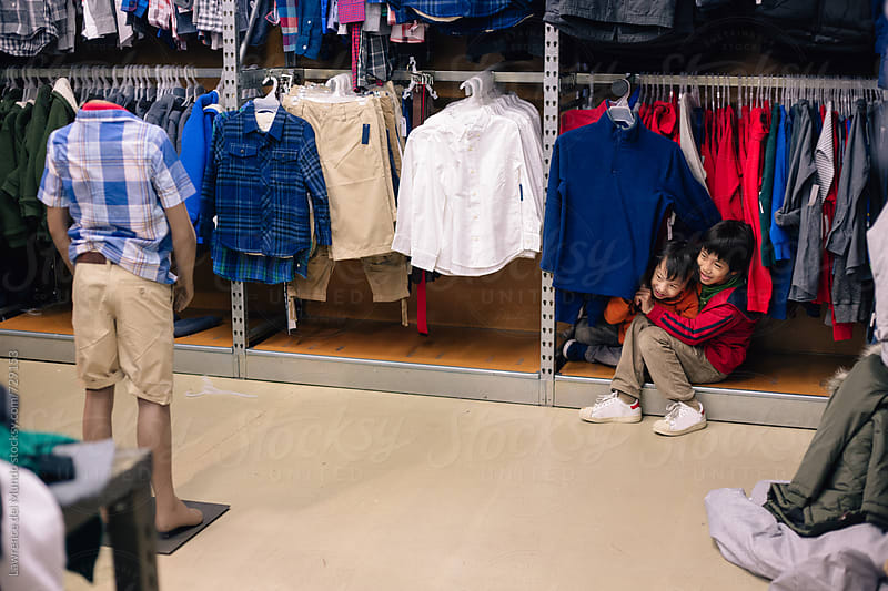 Two kids having too much fun inside a store  by Lawrence del Mundo for Stocksy United