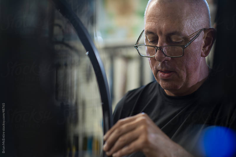 Local Bike Shop: Owner Seen Through Shelves of Parts Adjusting Wheel by Brian McEntire for Stocksy United