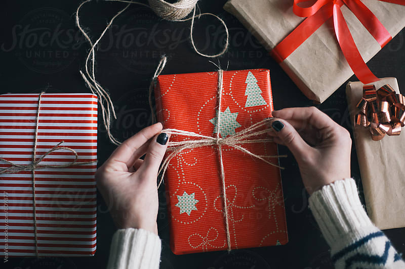 Female hands wrapping Christmas presents  by Marija Mandic for Stocksy United