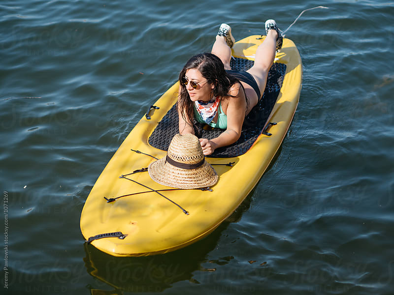 Young mixed race Asian woman relaxing on paddle board in lake water by Jeremy Pawlowski for Stocksy United