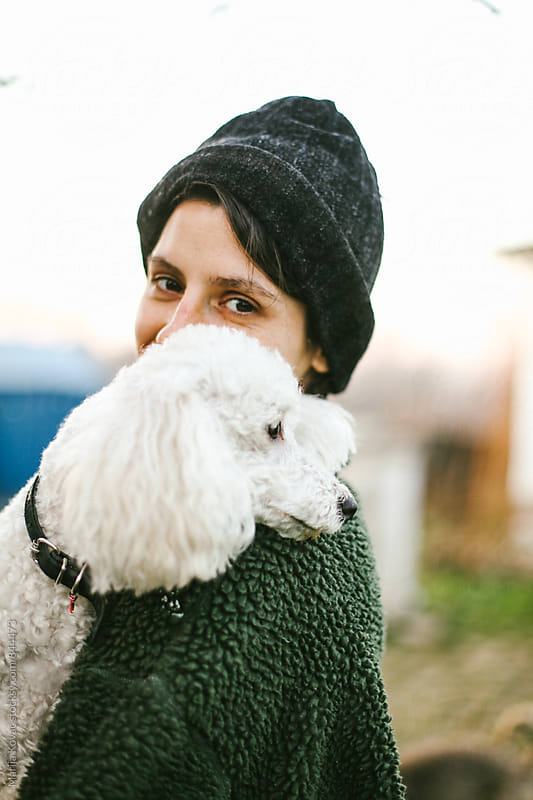 Happy woman holding her white poodle outdoor by Marija Kovac for Stocksy United