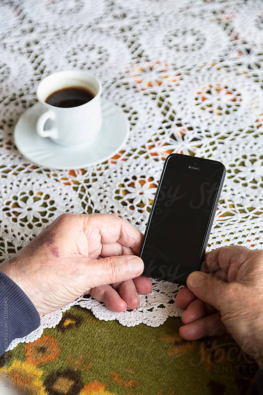 Hands of an old man holding touchscreen cellphone by Jovana Milanko for Stocksy United