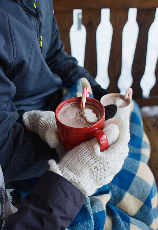 couple holding cups of cocoa on a porch in winter by Tana Teel for Stocksy United
