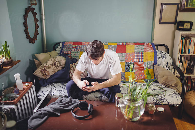Man Texting on Smartphone on his Couch at Home by Joselito Briones for Stocksy United