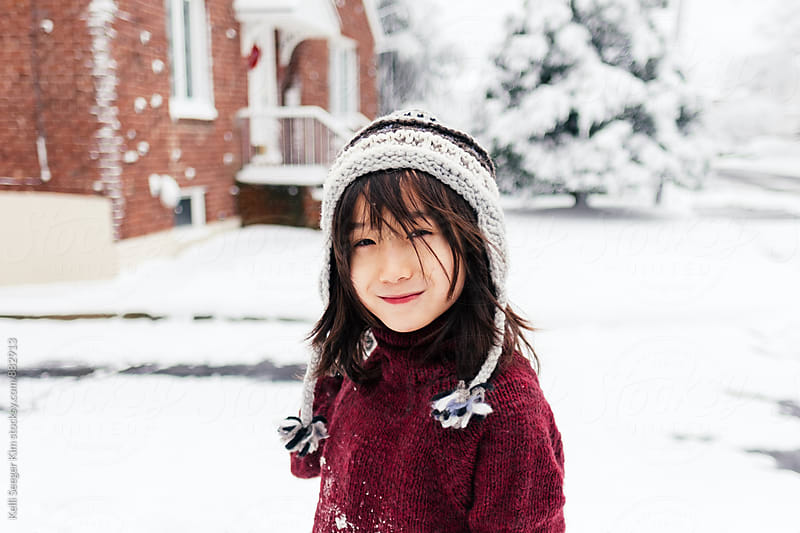 Young boy in winter hat smirks at camera by kelli kim for Stocksy United