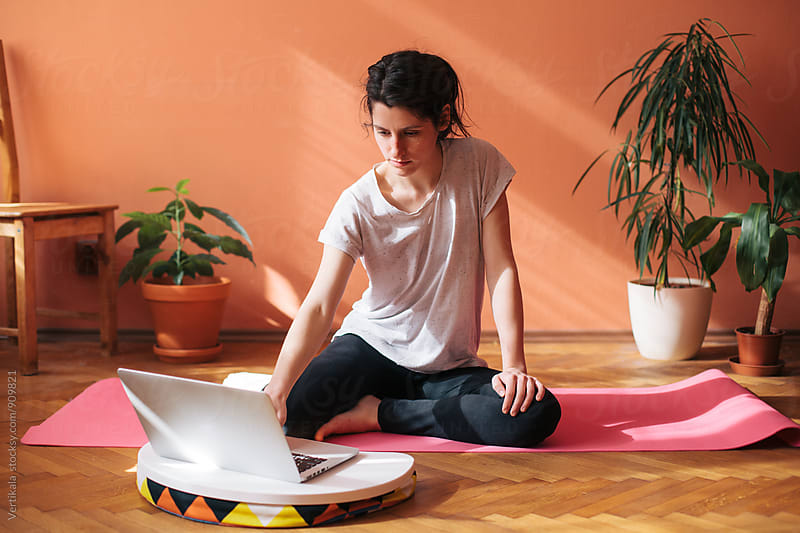 Woman having home yoga class by Marija Mandic for Stocksy United